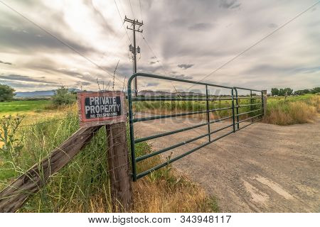 Security Gate And Fence With No Trespassing Sign Against Mountain And Cloudy Sky