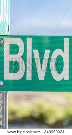 Vertical Selective Focus On A Green And White Road Street Sign That Reads Blvd