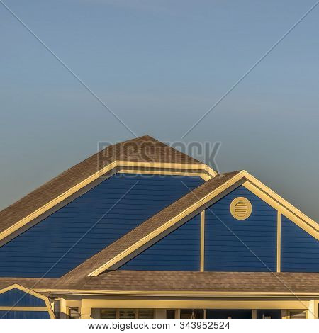 Square Close Up Of Roof Structure Of Home With Blue Gable Wall And Round Gable Window