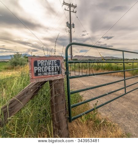 Square Security Gate And Fence With No Trespassing Sign Against Mountain And Cloudy Sky