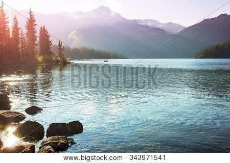 Serene scene by the mountain lake in Canada with reflection of the rocks in the calm water.