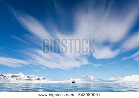 Boat on the fjords of Svalbard, a Norwegian archipelago between mainland Norway and the North Pole, with snowy mountains and vast blue sky background.