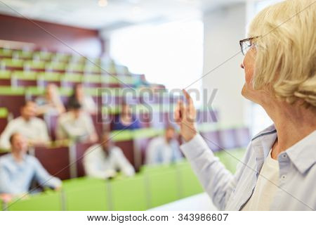 Senior woman as university lecturer teaching didactics in school lecture hall