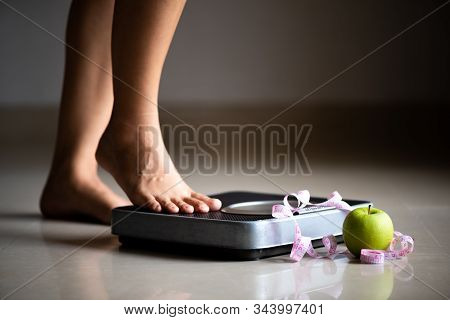 Female Leg Stepping On Weigh Scales With Measuring Tape And Green Apple. Healthy Lifestyle, Food And