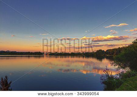 Sonnenuntergang Im Sommer An Einem See Mit Spiegelungen Der Wolken.
