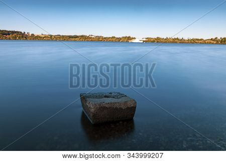 Sonnenuntergang Im Sommer An Einem See Mit Einem Stein Im Vordergrund.