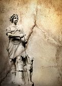 Old stone background with a sculpture man with dog poster