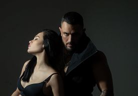 Muscular Man. Couple In Love On Dark Background. Relax. Fashion Studio Photo Of Beautiful Couple. Co