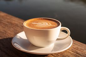 Close Up A Coffee Latte In White Cup And Milk Froth Above To Drink On Brown Wooden Table Background,