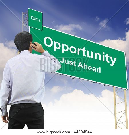 Businessman talking the phone standing in front Road sign concept with the text Opportunity poster