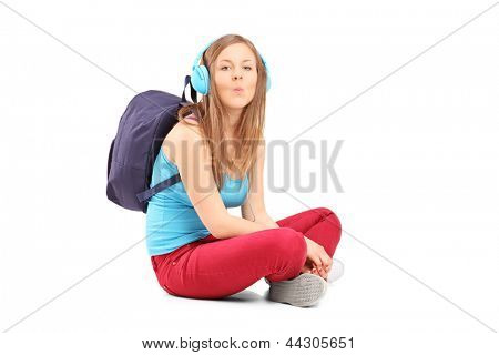 A schoolgirl with speakerphones sitting on a floor and giving kisses isolated on white background