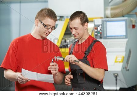 manufacture technician workers discussing and measure detail near cnc milling machine center at tool workshop