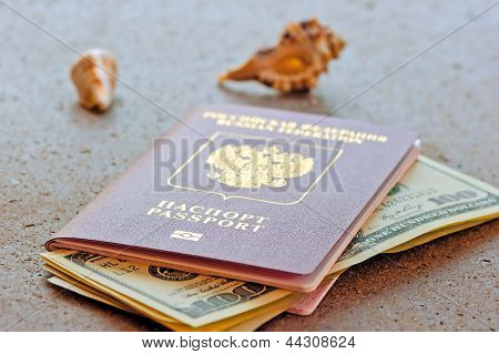 Russian passport with a dollar invested and seashells on a granite table top