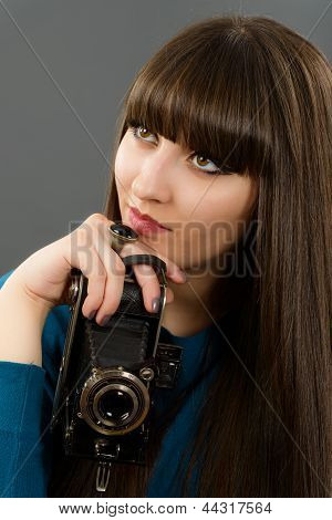 Retro Looking Young Beautiful Woman Holding A Vintage Retro Camera.