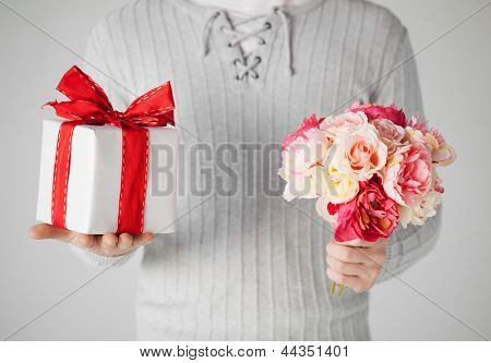 close up of man holding bouquet of flowers and gift box.