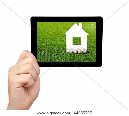 Isolated Man Hand Holding A Tablet With Grass And A House On The Screen