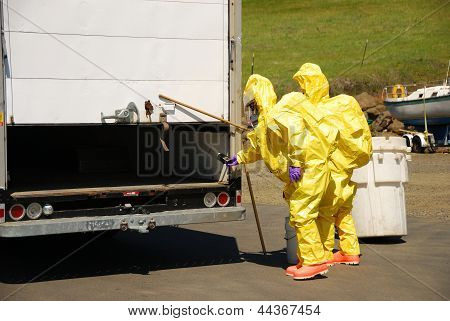 Fire fighters making entry on a truck leaking fluid The hazardous materials team trains on a recent corrosive drill in Roseburg Oregon. poster