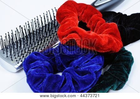 Four velvet hair scrunchies and a hairbrush against a white background. poster
