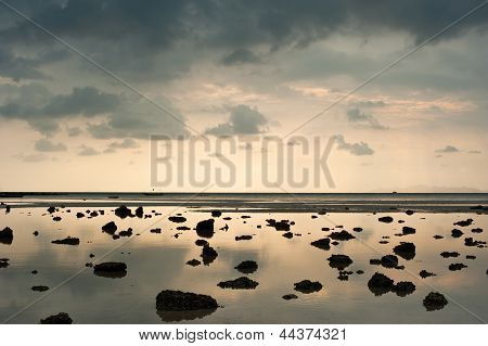 Sunset At Tropical Beach. Cay And Rocks At The Ocean Coast Under Evening Sun At High Tide. Thailand
