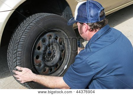Auto mechanic removing the tire from a car.