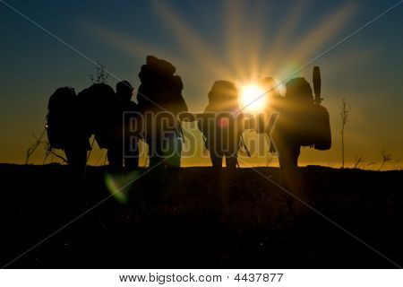 Hikers Walk In Sunset With Sunbeams And Reflections