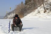Fisherman on winter fishing is fishing on the river poster