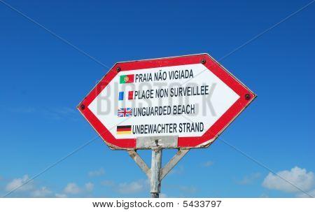Sign At The Beach (unguarded Beach) Against Blue Sky