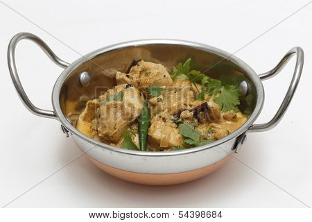 A kadai serving bowl of balti chicken pasanda curry, garnished with coriander leaves and a green chilli. This curry is made with yoghurt , cream and chopped coriander as well as the usual spices,