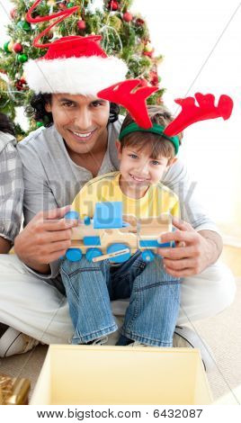 Father and son playing with a Christmas present at home poster