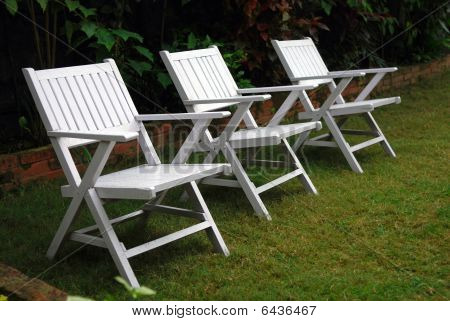 three chairs on green lawn in the garden