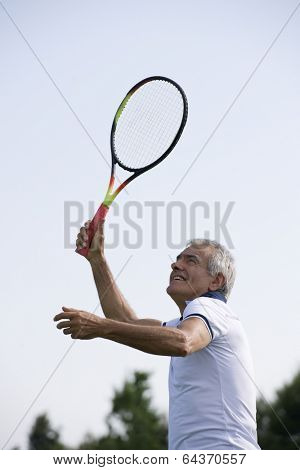 Happy senior man playing tennis, low angle view