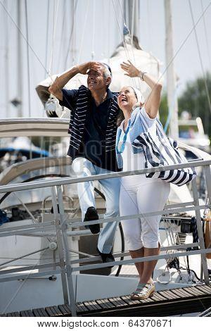 Senior happy couple walking on a dock in summer
