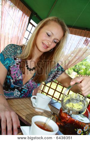 The Girl Pours In A Cup Tea