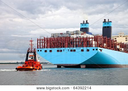 Container ship arriving at port assisted by tugboat. poster