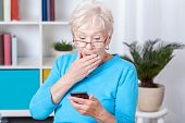 Elderly woman surprised by recieved text message poster