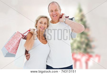 Couple with shopping bags against blurry christmas tree in room poster