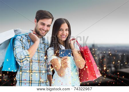 Couple with shopping bags and credit card against high angle view of city skyline poster