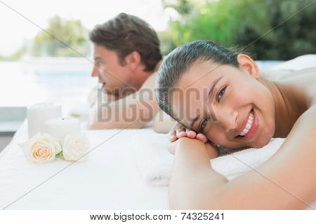 Portrait of relaxed young couple lying on massage table at spa center