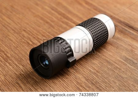 Modern monocular on wooden background