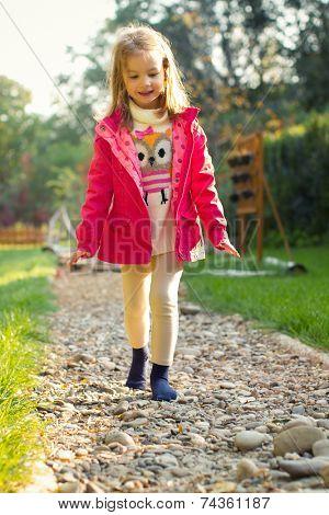 Five year old girl walking over pebbles. Sensory Discovery Walk. Sensory garden.