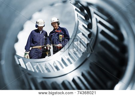 two engineers seen through a large cogwheels gear shaft, metal industry