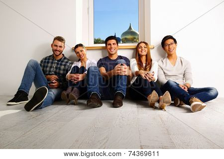 Portrait of a happy people sitting on the floor