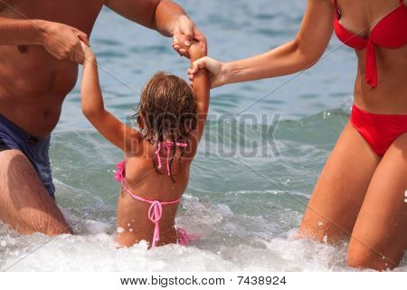 young family bathes in sea.