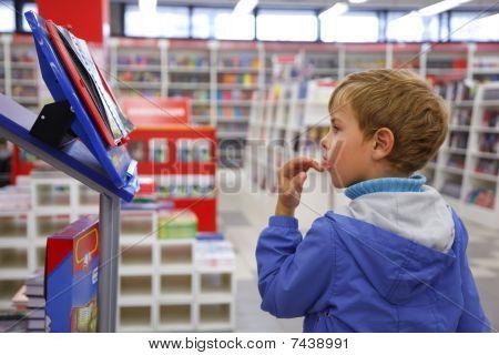 Librería niño en chaqueta azul con sorpresa mira en vitrina.