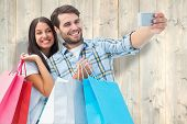 Happy couple taking a selfie against pale wooden planks poster