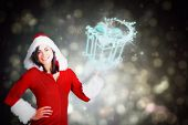 Pretty girl presenting in santa outfit against black abstract light spot design poster