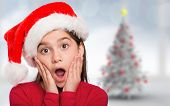 Festive little girl looking surprised against blurry christmas tree in room poster