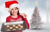 Festive little girl offering cookies against blurry christmas tree in room poster