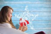 Pretty blonde relaxing on the couch with gift against blurred wooden planks poster