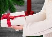 Woman offering a gift box against festive bow over wood poster